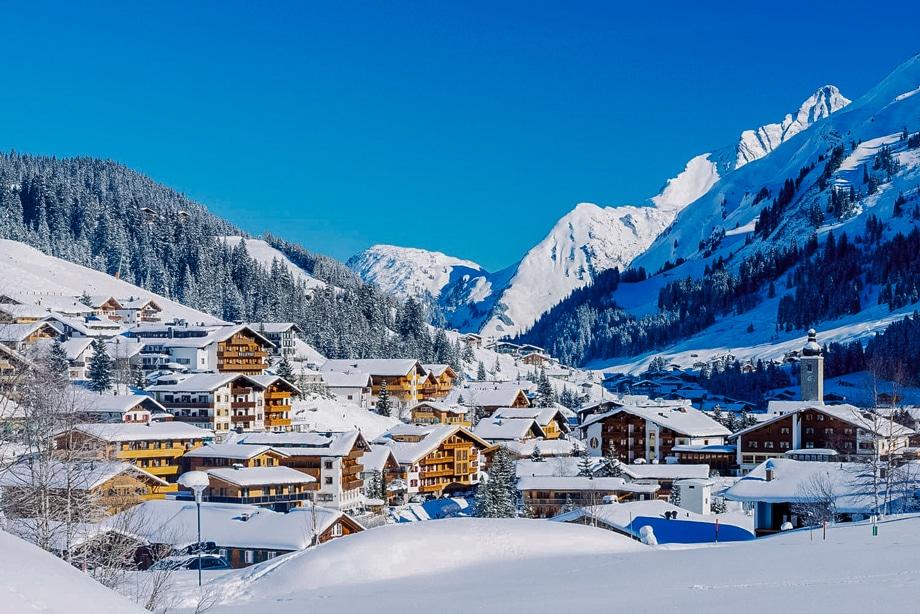 Вид на заснежанный зимний курорт в автрийских Альпах с вершинами гор и гостиницами для туристов