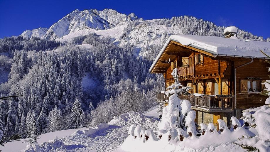 Заснежанные зимние Альпы и деревянный туристический домик для отдыхающих на австрийском горнолыжном курорте